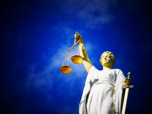 Statue of lady justice holding scales of justice and sword, deep blue sky in background with wispy clouds.